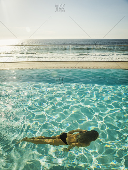 Woman swimming in pool by ocean