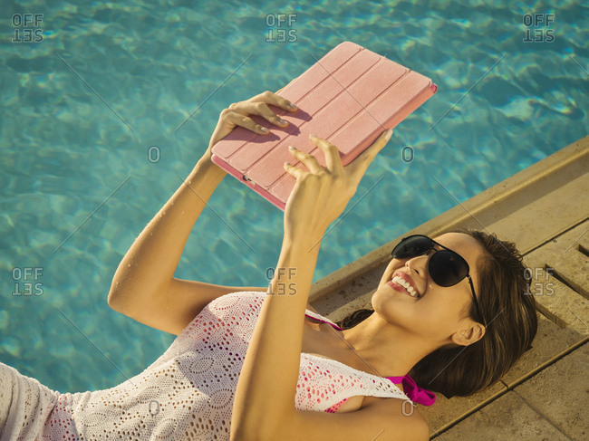 Woman using digital tablet by swimming pool