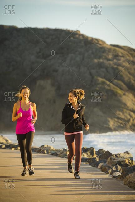 Two women jogging along sea