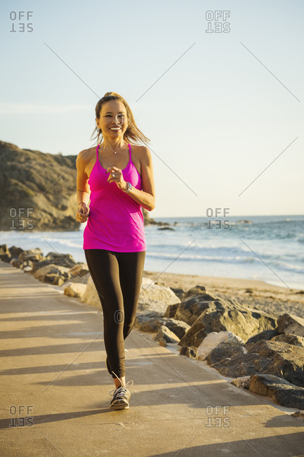 Woman jogging along sea