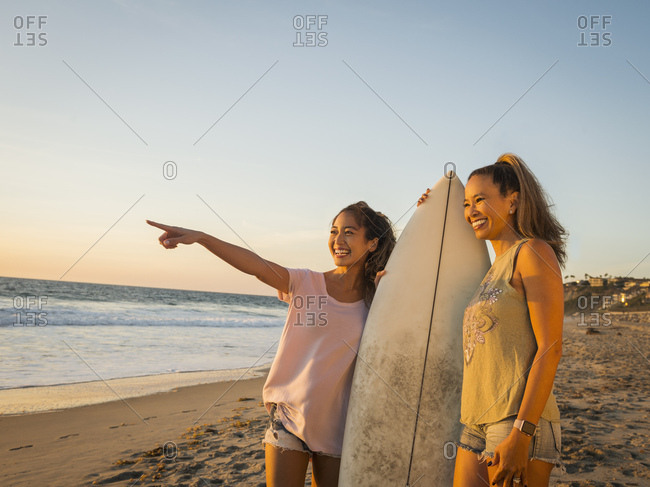 Mother and daughter with surfboard