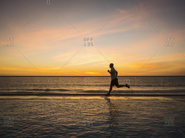 Man jogging along poolside - Offset