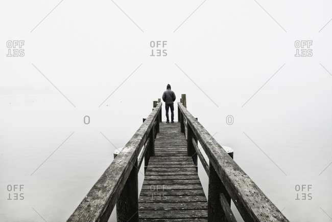 USA, Massachusetts, Cape Cod, Eastham, Man standing on jetty in fog