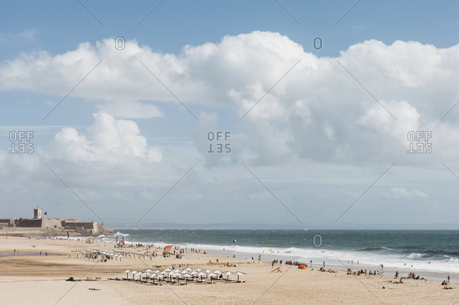 Portugal, Carcavelos, Puffy white clouds over beach