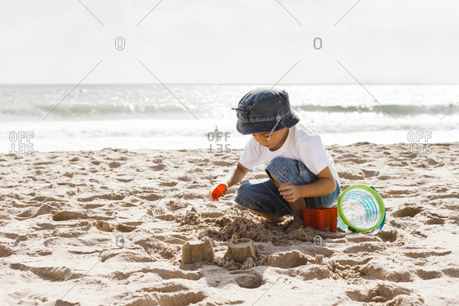 Boy (4-5) playing on beach