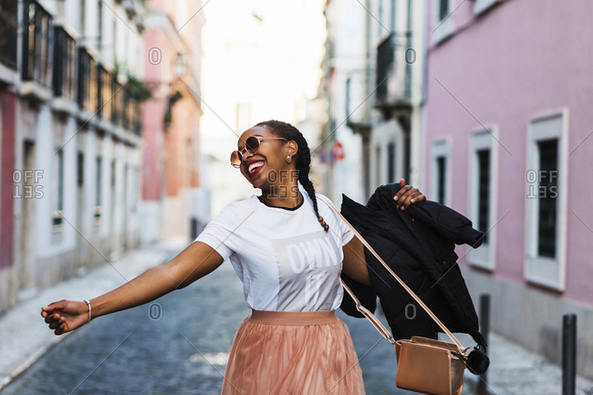 Portugal, Lisbon, Smiling young woman dancing in old town