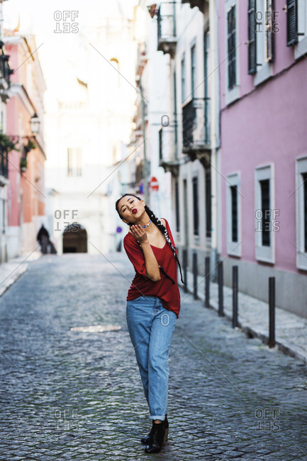 Portugal, Lisbon, Young woman blowing kiss in old town