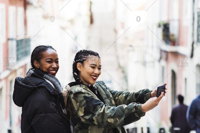Two young women taking selfie outdoors