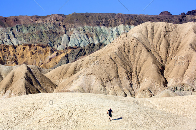Person on barren slope in mountain range with various minerals and colors in Death Valley