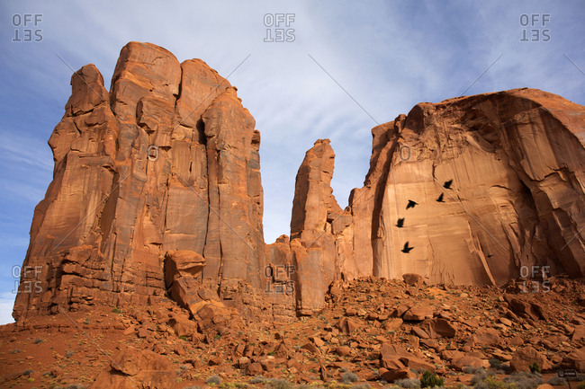 Shadows of flying crows against butte in Monument Valley