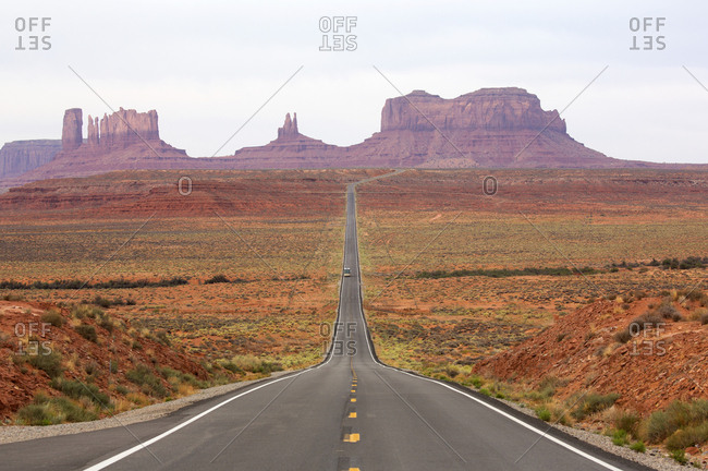 View of two lane highway through Monument Valley