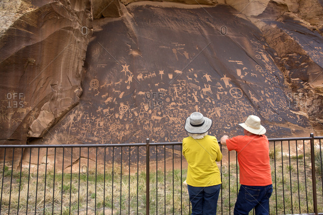 Moab, Utah, USA - May 7, 2018: Tourists viewing petroglyphs at Newspaper Rock