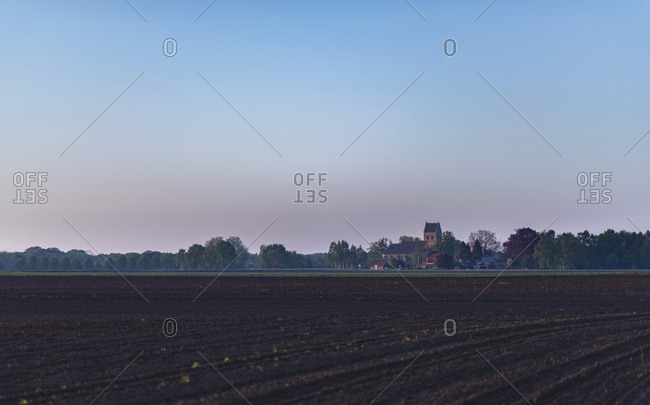 Agricultural field with church of village on horizon at sunrise.