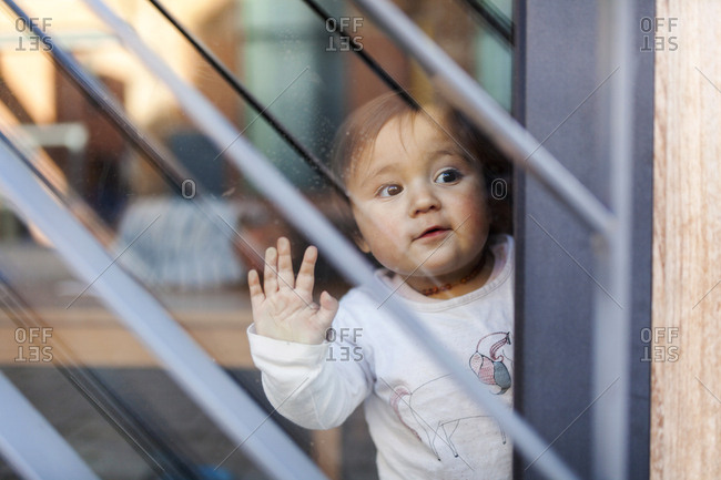 Curious toddler peering out window alone