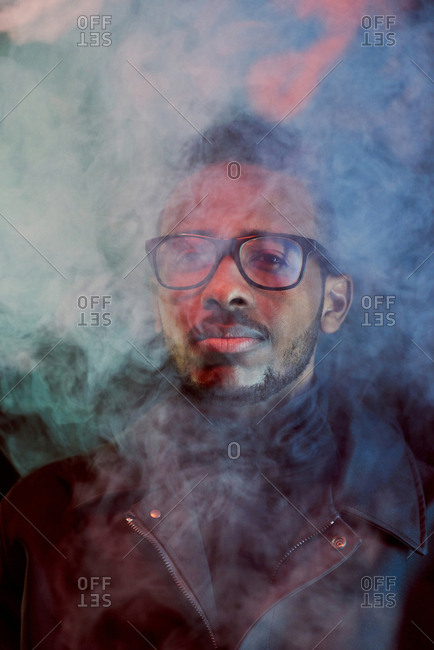 Portrait of stylish African American guy in leather jacket and glasses standing in cloud of smoke and looking at camera