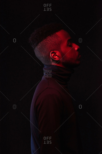 Profile portrait of young handsome African American man with stylish haircut standing in the dark with his eyes closed