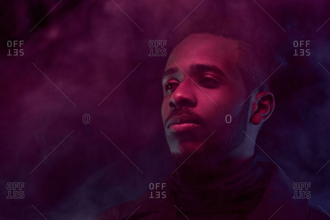 Portrait of young attractive Black man standing in purple smoke cloud in the dark and looking into the distance thoughtfully, low angle view