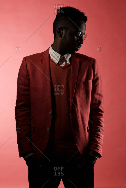 Portrait of African American man in fashionable suit standing in dark studio with faint red illumination and looking away