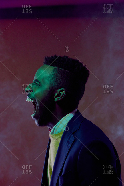 Profile portrait of young stylish Black guy getting rid of negative emotions. Freaked out man expressing his rage by yelling alone in the dark