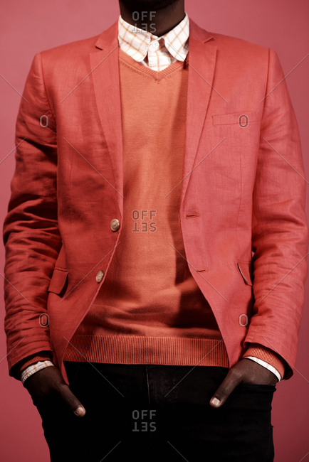 Unrecognizable fashionable Black man in jeans, pullover and linen jacket standing against red background with hands in pockets