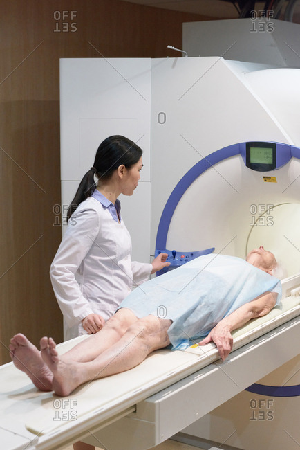 Female doctor standing by elderly woman lying on movable bed and getting ready for MRI procedure in modern clinic