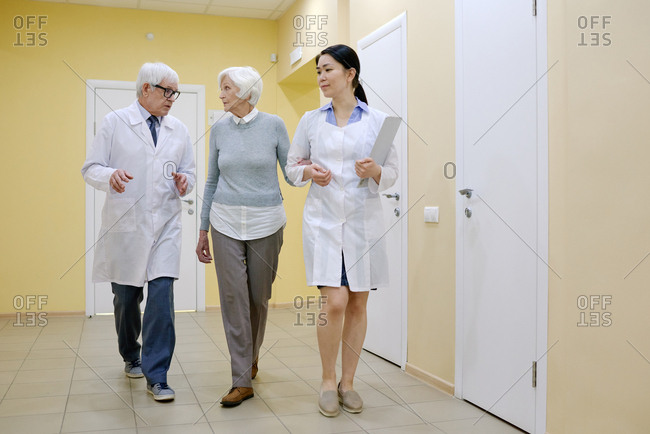 Caucasian elderly woman listening to doctors while they walking down the corridor in hospital after medical examination