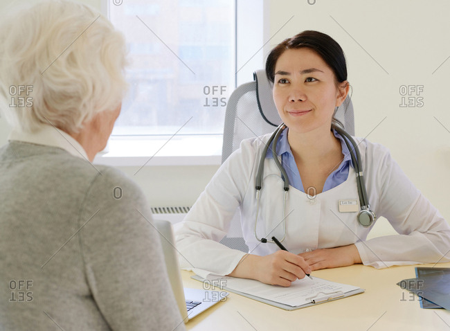 Elderly woman having medical consultation in hospital. Young Asian female physician listening attentively to senior patient and smiling in friendly manner