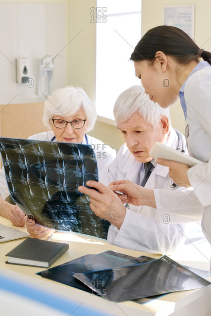 Group of experienced doctors looking at X-ray of patient after MRI examination and analyzing results together in consulting room