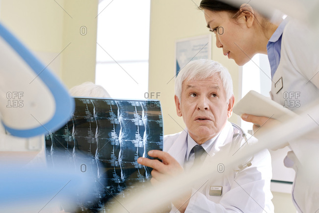 Mature male radiologist examining X-ray of patient after MRI procedure and consulting with young female assistant in clinic