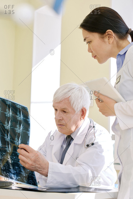 Mature male physician looking at radiograph of patient after MRI scan and analyzing his health conditions with young female assistant