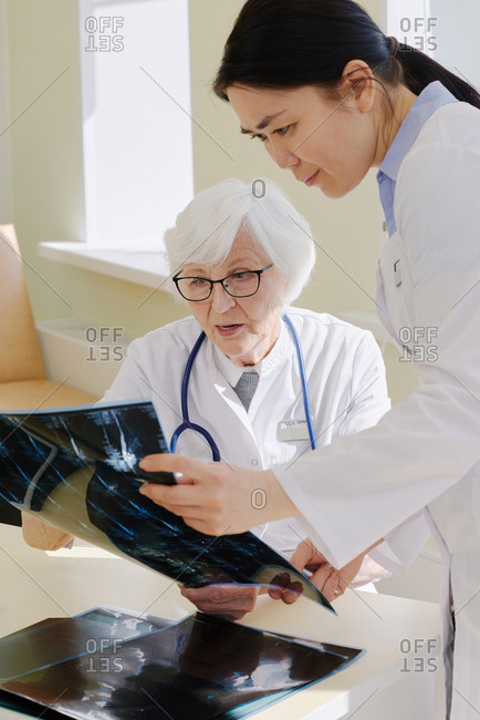 Mature female radiologist and her younger assistant examining X-ray of patient after MRI procedure and analyzing results together
