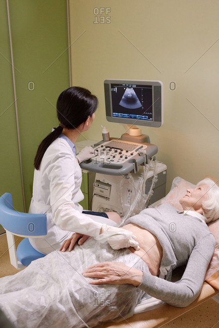 Caucasian elderly woman having abdominal ultrasound in clinic. Female doctor using ultrasonic scan and looking at computer while examining abdomen of senior patient