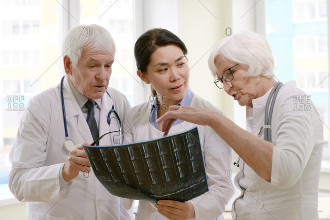 Group of experienced male and female doctors examining X-ray of patient after MRI test in hospital, analyzing results and discussing treatment