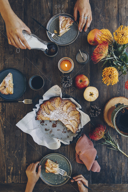 Top view of two people's hands sharing meal at dark wooden table with fall themed decor