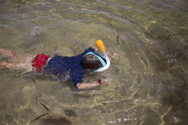 Top view of little brunette bow practicing snorkeling in shallow water