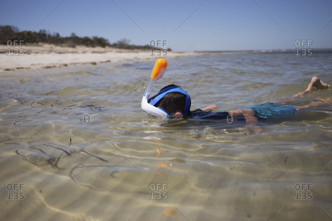 Small boy swimming under water with plastic snorkeling kit