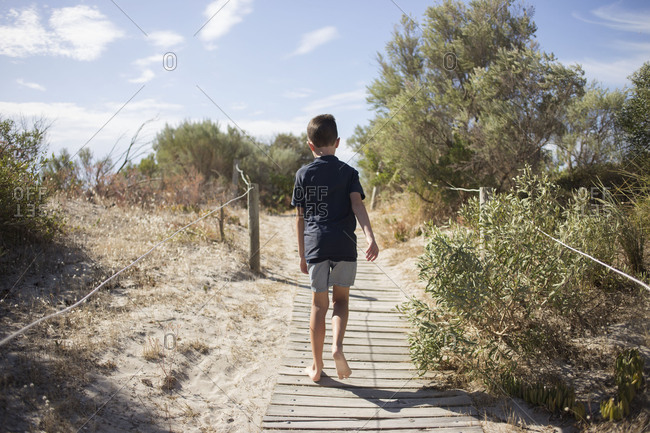 Boy wandering down beachside path alone on sunny day
