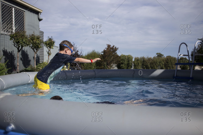 Brunette kid wearing goggles in mid dive at backyard pool