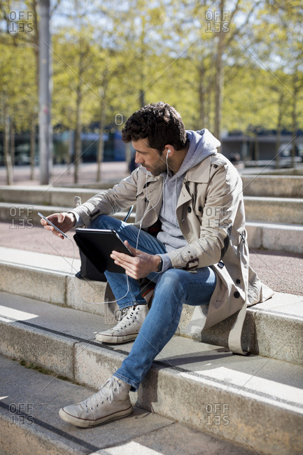 Businessman sitting outdoor, using technology  in the city. Barcelona, Spain.