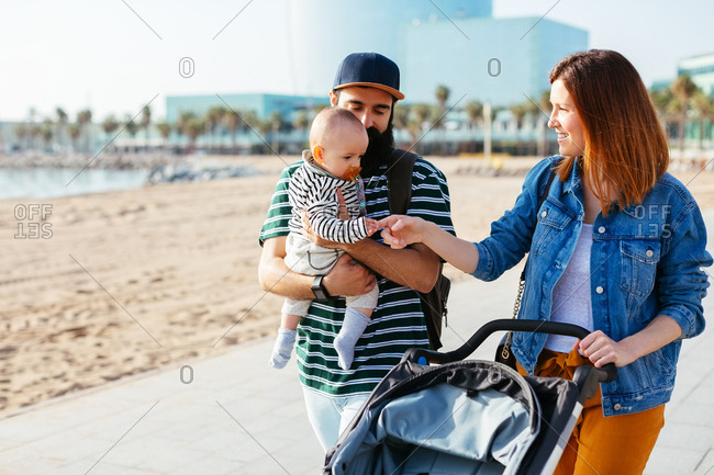 Couple on a walk with their baby and stroller near the beach.