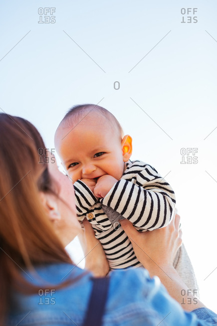 Baby boy smiling with his mother.