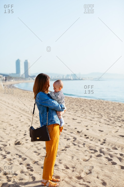 Mother holding baby boy on the beach.