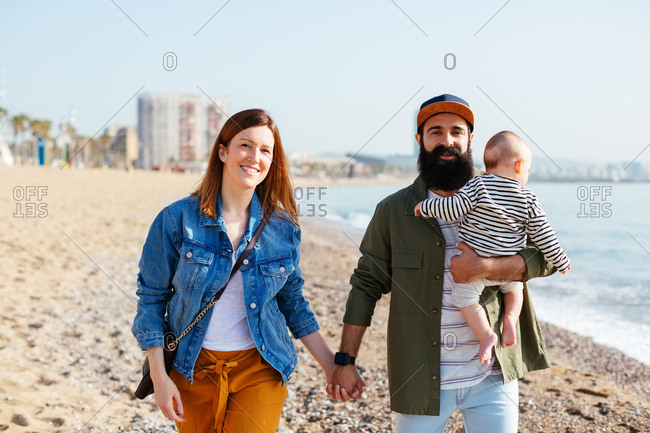 Young parents holding their baby walking on the beach.