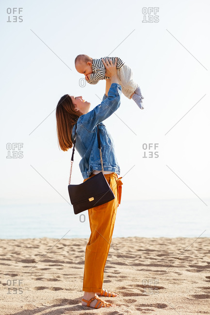 Side view of mother holding her baby boy on the beach.