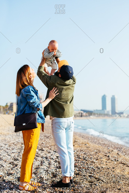Back view of parents holding their baby on the beach.