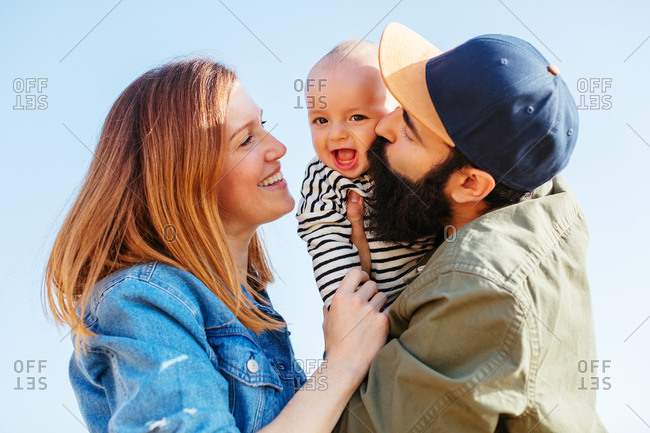 Portrait of couple kissing their baby boy.