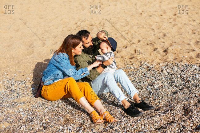 Couple with their baby sitting on the beach.