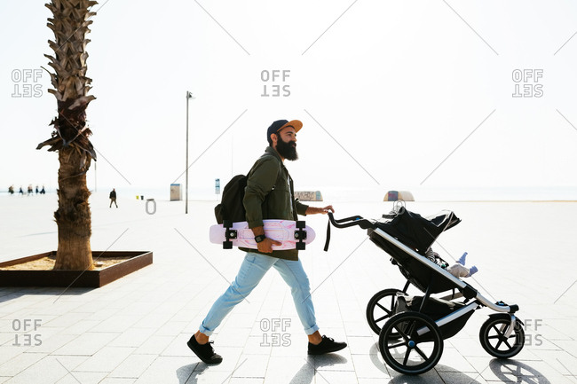 Father holding skateboard on a walk with his baby in stroller.