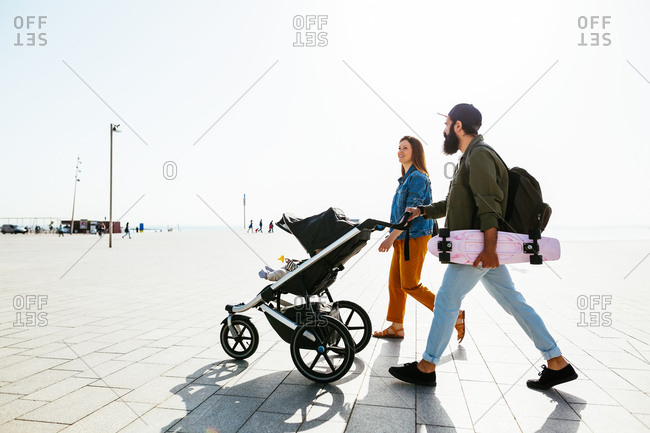 Side view of parents on a walk with their baby in stroller.