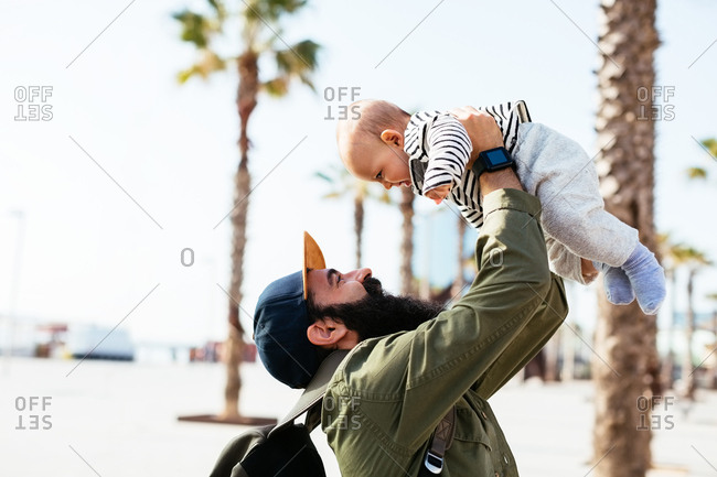 Father holding his baby boy on the street.